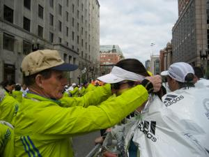 A volunteer putting my race medal around my neck at the finish line of the Boston Marathon.
