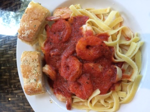 Shrimp in marinara sauce over noodles and a side of garlic bread