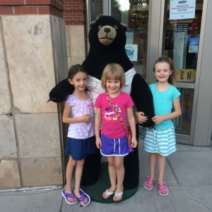 The twins and Allen's daughter Sara posing with a stuffed bear.