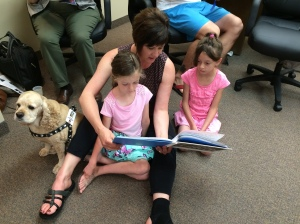 Sitting in the shelter at the public library with the nieces, Isabella's teacher, and her classroom dog, A